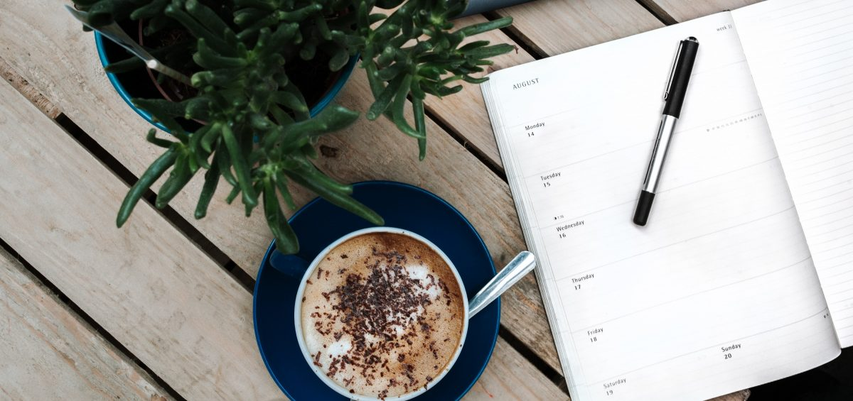 Coffee and diary on a wooden table